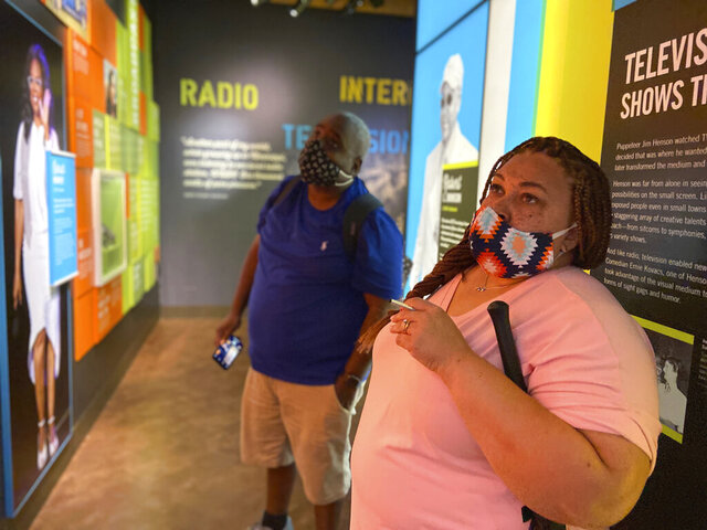 Edward Powe and Sharonda Powe view an exhibit on Wednesday, July 1, 2020 at The Mississippi Arts + Entertainment Experience in Meridian, Miss., where guests are asked to wear masks and practice social distancing during their visit. Miss. Gov. Tate Reeves is urging the public to follow those guidelines to stop the spread of COVID-19. (Bill Graham/The Meridian Star via AP)