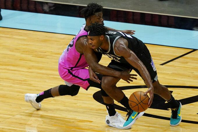 Miami Heat forward Jimmy Butler (22) defends Sacramento Kings guard Buddy Hield (24) during the second half of an NBA basketball game, Saturday, Jan. 30, 2021, in Miami. (AP Photo/Marta Lavandier)