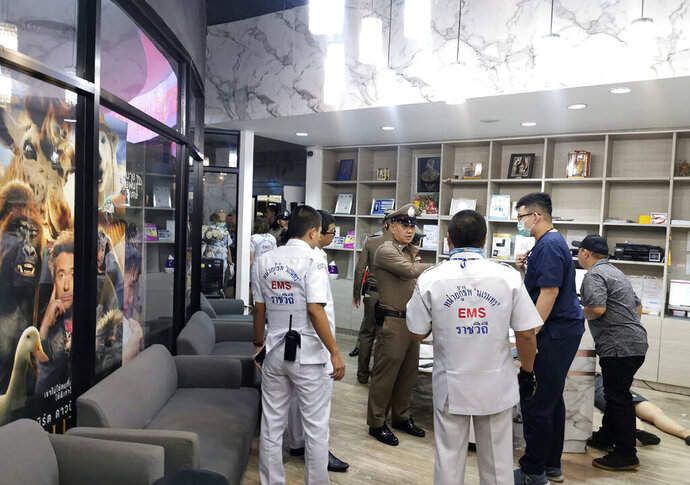 Security officers inspect the scene of a shooting in Bangkok, Thailand, Tuesday, Feb. 18, 2020. Gun violence has struck again at a shopping mall in Thailand, where a man in the nation's capital Bangkok on Tuesday  shot dead one woman working at a beauty clinic and wounded another. The motive for the shooting was believed to be jealousy, and the suspected shooter escaped from the scene and remained  at large several hours later. (Pho Koo 19 Volunteer, Ruam Duay Chuay Kan charity radio network via AP)
