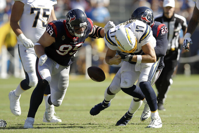 Houston Texans defensive end J.J. Watt, left, and outside linebacker Whitney Mercilus, right, force Los Angeles Chargers quarterback Philip Rivers to fumble during the second half of an NFL football game Sunday, Sept. 22, 2019, in Carson, Calif. (AP Photo/Marcio Jose Sanchez)