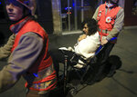 FILE - In this Friday Nov. 13, 2015 file photo a woman is evacuated from the Bataclan theater after a shooting in Paris. (AP Photo/Thibault Camus, File)