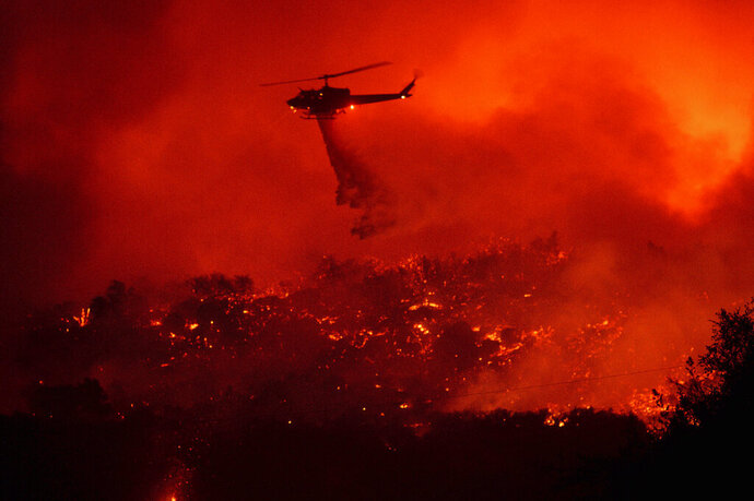 A helicopter drops water on the Cave Fire burning along Highway 154 in Los Padres National Forest, Calif., above Santa Barbara on Tuesday, Nov. 26, 2019. (AP Photo/Noah Berger)