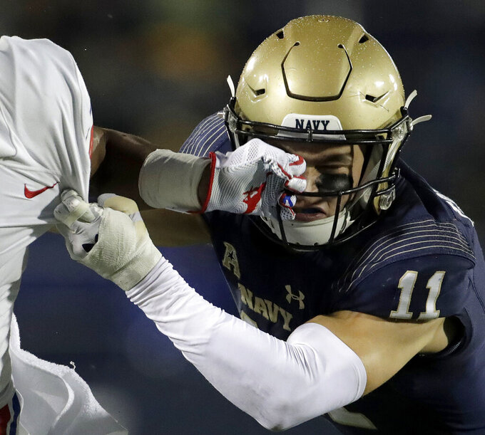 SMU wide receiver CJ Sanders, left, grabs the face mask of Navy safety Evan Fochtman while running with the ball during the first half of an NCAA college football game, Saturday, Nov. 23, 2019, in Annapolis, Md. (AP Photo/Julio Cortez)