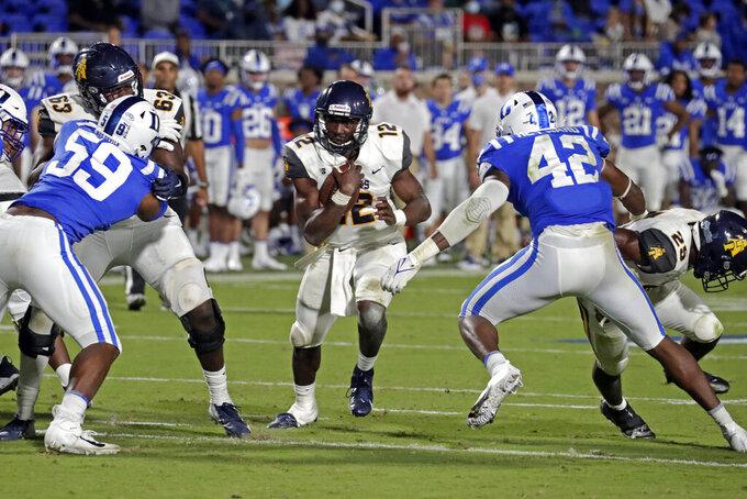 North Carolina A&T quarterback Kingsley Ifedi (12) runs against Duke defensive end Michael Reese (59) and linebacker Shaka Heyward (42) during the second half of an NCAA college football game in Durham, N.C., Friday, Sept. 10, 2021. (AP Photo/Chris Seward)
