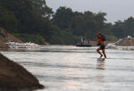 A migrant walks across the Suchiate River from Guatemala into Mexico, near Ciudad Hidalgo, Chiapas State, Mexico, Friday, Jan. 17, 2020. United States officials are crediting tough measures taken over the past year and cooperation from regional governments for sharply reducing the number of Central American migrants who responded to a call for a new caravan.  (AP Photo/Marco Ugarte)