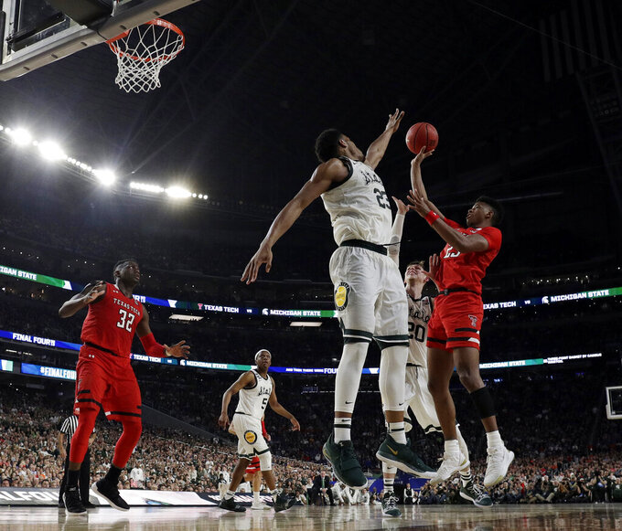 Texas Tech's Jarrett Culver (23) takes a shot against Michigan State's Xavier Tillman (23) and Matt McQuaid (20) during the second half in the semifinals of the Final Four NCAA college basketball tournament, Saturday, April 6, 2019, in Minneapolis. (AP Photo/David J. Phillip)