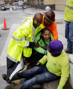 Workers are helped after a large portion of a hotel under construction suddenly collapsed in New Orleans on Saturday, Oct. 12, 2019. Several construction workers had to run to safety as the Hard Rock Hotel, which has been under construction for the last several months, came crashing down. It was not immediately clear what caused the collapse or if anyone was injured.  (Scott Threlkeld/The Advocate via AP)