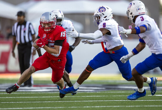 New Mexico wide receiver Luke Wysong (15) avoids the tackle attempt by Houston Baptist cornerback Kenneth Kemp (9) during the first half of an NCAA college football game Thursday, Sept. 2, 2021, in Albuquerque, N.M. (AP Photo/Andres Leighton)