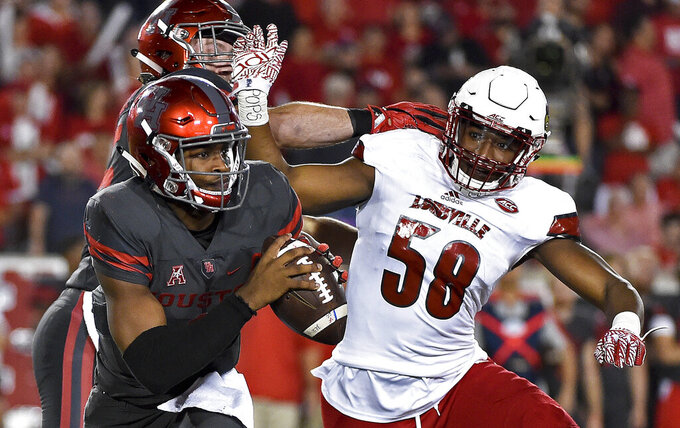 FILE - In this Nov. 17, 2016, file photo, Houston quarterback Greg Ward Jr., left, scrambles past Louisville linebacker Jonathan Greenard (58) during the second half of an NCAA college football game in Houston. Greenard's 2018 season ended after nine plays, cut short on Louisville's opening defensive series when he dislocated his right wrist and tore several ligaments in a 51-14 loss to Alabama. Greenard opted to leave Louisville after coach Bobby Petrino was fired in November, scrambled to complete his degree and ended up at Florida as a graduate transfer. Now, he's expected to start for the eighth-ranked Gators when they usher in the college football season against rival Miami on Saturday night. (AP Photo/Eric Christian Smith, File)