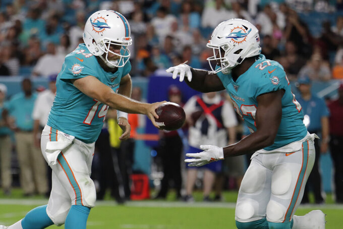 Miami Dolphins quarterback Ryan Fitzpatrick (14) hands off to running back Kalen Ballage (27) during the first half of an NFL football preseason game against the Jacksonville Jaguars, Thursday, Aug. 22, 2019, in Miami Gardens, Fla. (AP Photo/Lynne Sladky)