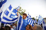 Supporter wave Greek flags during New Democracy party final election campaign rally in Athens, Thursday, July 4, 2019. Greeks head to the polls in early general elections on Sunday, July 7. (AP Photo/Thanassis Stavrakis)
