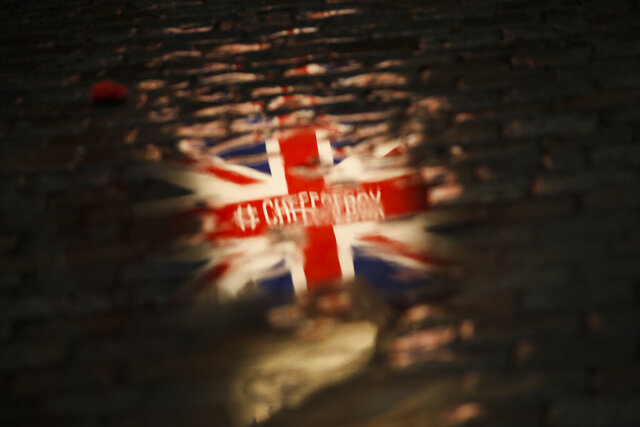 The Union flag is reflected in a puddle during an event called