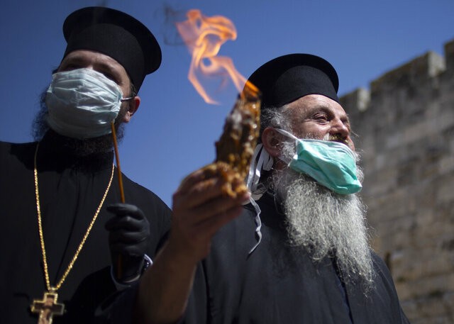 An Orthodox clergyman holds holy fire to transfer to predominantly Orthodox countries from the Church of the Holy Sepulchre, traditionally believed by many Christians to be the site of the crucifixion and burial of Jesus Christ, in Jerusalem's old city after the traditional Holy Fire ceremony was called off amid coronavirus, Saturday, April 18, 2020. A few clergymen on Saturday marked the Holy Fire ceremony as the coronavirus pandemic prevented thousands of Orthodox Christians from participating in one of their most ancient and mysterious rituals at the Jerusalem church marking the site of Jesus' tomb.(AP Photo/Ariel Schalit)