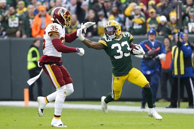 Green Bay Packers' Aaron Jones runs past Washington Redskins' Montae Nicholson during the first half of an NFL football game Sunday, Dec. 8, 2019, in Green Bay, Wis. (AP Photo/Mike Roemer)