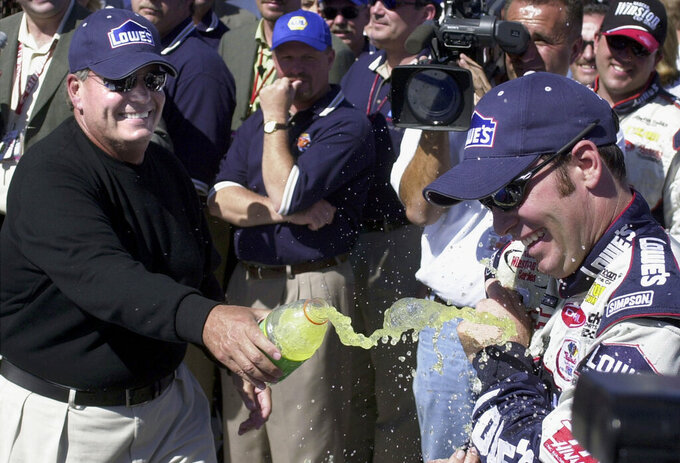 FILE - In this April 28, 2002, file photo, winner Jimmie Johnson, right, gets cooled off by car owner Rick Hendrick as they celebrate in Victory Lane after Johnson won the NASCAR auto race at California Speedway in Fontana, Calif. When Johnson won his first NASCAR Cup Series race at Fontana 18 years ago, this famously worn-out asphalt track had a whole lot less wear and tear. So did Johnson, who is visiting his home track this weekend for the last time as a full-time driver. (AP Photo/Will Lester, File)