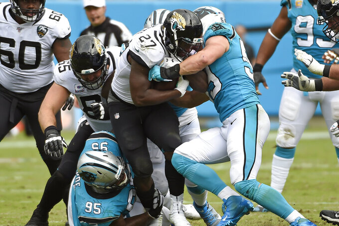Carolina Panthers defensive tackle Dontari Poe (95) and middle linebacker Luke Kuechly (59) tackle Jacksonville Jaguars running back Leonard Fournette (27) during the second half of an NFL football game in Charlotte, N.C., Sunday, Oct. 6, 2019. (AP Photo/Mike McCarn)