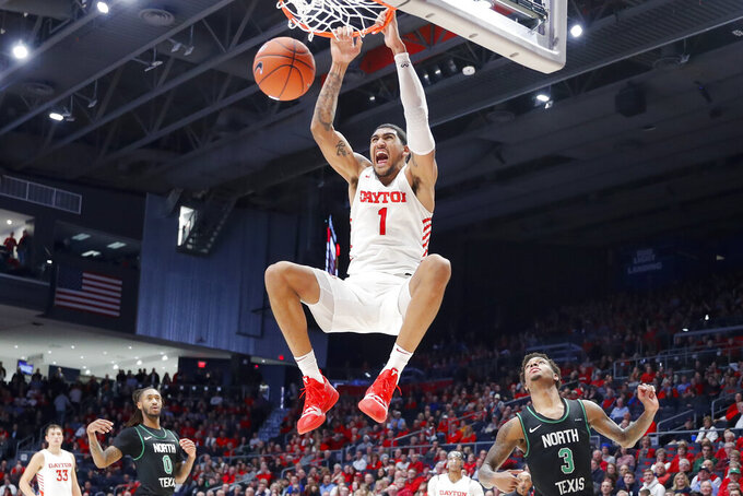 Dayton's Obi Toppin (1) dunks as North Texas' Javion Hamlet (3) looks on during the second half of an NCAA college basketball game, Tuesday, Dec. 17, 2019, in Dayton, Ohio. (AP Photo/John Minchillo)