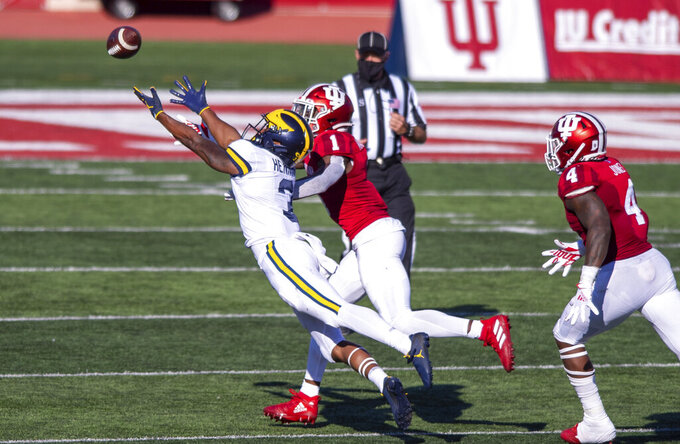 Michigan wide receiver A.J. Henning (3) makes a diving effort for the ball as he's defended by Indiana defensive back Devon Matthews (1) during the second half of an NCAA college football game Saturday, Nov. 7, 2020, in Bloomington, Ind. Indiana won 38-21. (AP Photo/Doug McSchooler)