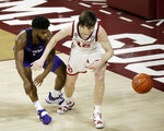Oklahoma's Austin Reaves (12) and TCU's Mickey Pearson Jr. (1) fight for the ball during the second half of an NCAA college basketball game in Norman, Okla., Tuesday, Jan. 12, 2021. (AP Photo/Garett Fisbeck)