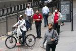 Commuters walk on Wall Street, Monday, Aug. 31, 2020, in New York. (AP Photo/Mark Lennihan)