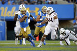 UCLA quarterback Dorian Thompson-Robinson, left, is chased by Arizona State defensive lineman T.J. Pesefea (44) during the first half of an NCAA college football game Saturday, Oct. 26, 2019, in Pasadena, Calif. (AP Photo/Marcio Jose Sanchez)