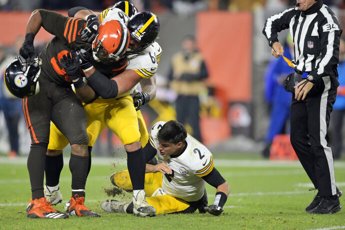 Cleveland Browns defensive end Myles Garrett (95) takes Pittsburgh Steelers quarterback Mason Rudolph's (2) helmet off during the second half of an NFL football game Thursday, Nov. 14, 2019, in Cleveland. (AP Photo/David Richard)