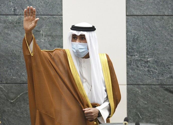 FILE - In this Sept. 30, 2020 file photo, the new Emir of Kuwait Sheikh Nawaf Al Ahmad Al Sabah, waves after he was sworn in at the Kuwaiti National Assembly in Kuwait. The state news agency said Wednesday, Oct. 7, 2020, that the deputy chief of the National Guard, who spent years in the oil-rich country's security services, was nominated as crown prince. The nomination makes Sheikh Meshal Al Ahmed Al Jaber Al Sabah the heir apparent to the 83-year-old new emir. But lawmakers must approve the chosen successor during its final session on Thursday, ahead of the formation of a new government. (AP Photo/Jaber Abdulkhaleg, File)
