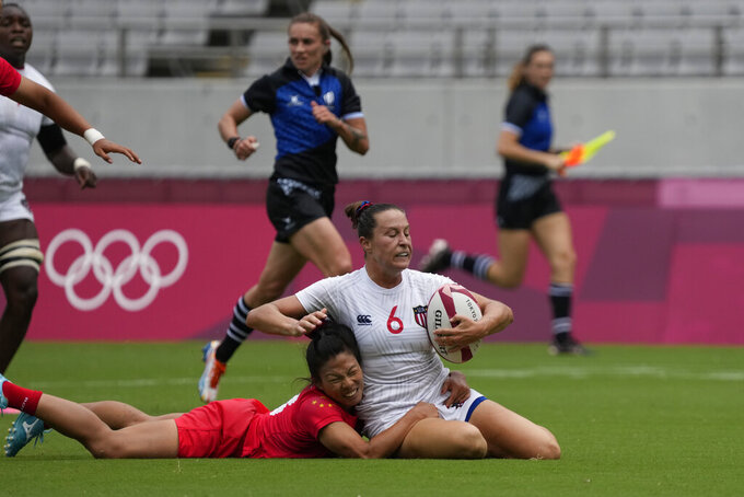 China's Liu Xiaoqian, left, brings down Lauren Doyle of the United States, in their women's rugby sevens match at the 2020 Summer Olympics, Thursday, July 29, 2021 in Tokyo, Japan. (AP Photo/Shuji Kajiyama)