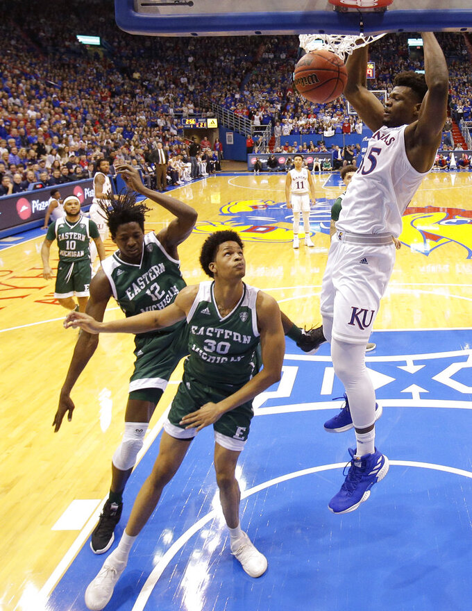 Kansas' Udoka Azubuike (35) gets past Eastern Michigan's Jalen King (30) to dunk the ball during the first half of an NCAA college basketball game Saturday, Dec. 29, 2018, in Lawrence, Kan. (AP Photo/Charlie Riedel)