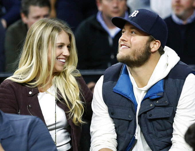 FILE - In this Nov. 17, 2015, file photo, Detroit Lions quarterback Matthew Stafford, right, smiles while watching the Detroit Pistons play the Cleveland Cavaliers with his wife Kelly, left, during the first half of an NBA basketball game, in Auburn Hills, Mich. Kelly Stafford says she is home after surgery to remove a brain tumor. She says the surgery lasted 12 hours and shared other details Sunday, April 21, 2019, on her Instagram account. (AP Photo/Duane Burleson, File)