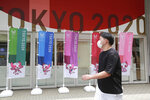 A man wearing a face mask to protect against the spread of the coronavirus walks by flags to promote the Olympic Games in Tokyo Monday, July 26, 2021. (AP Photo/Koji Sasahara)