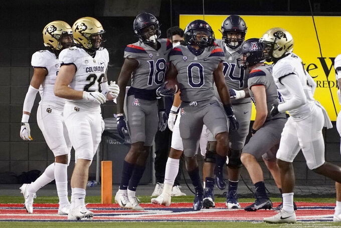 Arizona running back Gary Brightwell (0) celebrates with teammates after scoring a touchdown against Colorado during the first half of an NCAA college football game, Saturday, Dec. 5, 2020, in Tucson, Ariz. (AP Photo/Rick Scuteri)