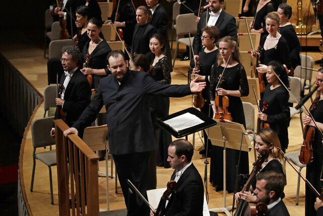 "FILE — In this Oct. 31, 2019, file photo, Andris Nelsons gestures towards the musicians prior to conducting a joint concert of the Boston Symphony Orchestra and Germany's visiting Leipzig Gewandhaus Orchestra, at Symphony Hall, in Boston. The orchestra has cancelled its coming tour of Asia amid concerns about the deadly virus in China. Andris Nelsons, the orchestra's music director, said Thursday, Jan. 30, 2020, that the decision was made out of concern for the ""health and well-being"" of its musicians.  (AP Photo/Elise Amendola, File)"