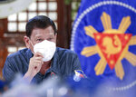 In this May 11, 2020, photo provided by the Malacanang Presidential Photographers Division, Philippine President Rodrigo Duterte, wearing a mask, gestures during a meeting at the Malacanang presidential palace in Manila, Philippines. The Philippine president says a massive lockdown that has restricted millions to their homes will be eased but warned those who will be allowed to go back to work to follow safeguards to avoid more deaths and a second wave of COVID-19 outbreaks. (Ace Morandante/ Malacanang Presidential Photographers Division via AP)