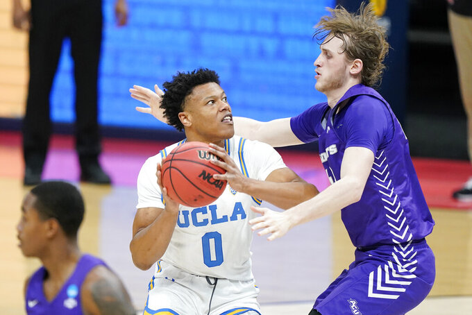 UCLA's Jaylen Clark (0) tries to get past Abilene Christian's Clay Gayman, right, during the first half of a college basketball game in the second round of the NCAA tournament at Bankers Life Fieldhouse in Indianapolis Monday, March 22, 2021. (AP Photo/Mark Humphrey)