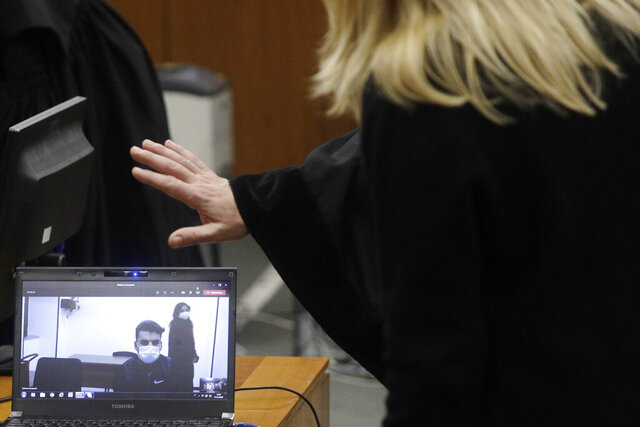 Gabriel Natale-Hjorth, right, connected from the jailhouse to the courtroom, is greeted by his mother Heidi Hjorth, during a hearing in the trial in which he is accused of killing paramilitary police officer Mario Cerciello Rega, in Rome, Thursday, Dec. 17, 2020. Finnegan Lee Elder and Gabriel Natale-Hjorth both from California are accused of murdering the police officer during a summer vacation in Italy in July 2019. (AP Photo/Gregorio Borgia, Pool)