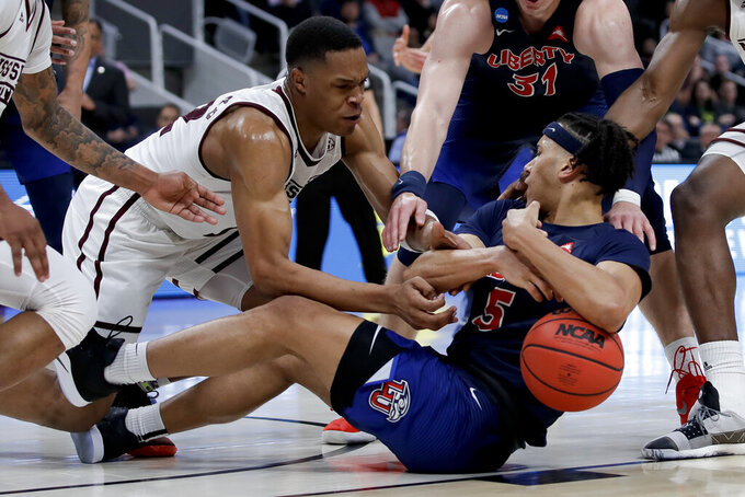 Mississippi State guard Robert Woodard, left, vies for a loose ball with Liberty forward Keenan Gumbs during the first half of a first-round game in the NCAA men's college basketball tournament Friday, March 22, 2019, in Columbia, S.C. (AP Photo/Ben Margot)