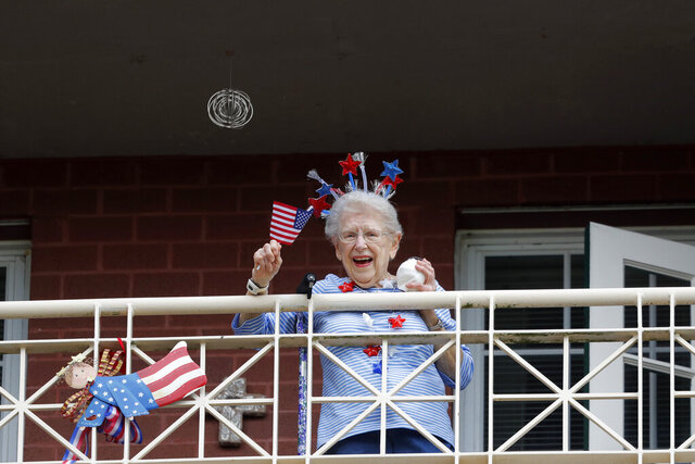 FILE - In this March 20, 2020, file photo, a resident of the Lambeth House, where a cluster of COVID-19 has formed, reacts from her balcony as opera singers Irini Hymel and Bryan Hymel sing to the quarantined residents in New Orleans. As coronavirus cases spike ever higher in Louisiana, the state's nursing homes, assisted living sites and adult residential care facilities are showing more and more