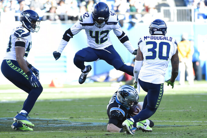 Carolina Panthers quarterback Kyle Allen (7) slides under Seattle Seahawks defensive back Lano Hill (42) strong safety Bradley McDougald (30) rushes in during the second half of an NFL football game in Charlotte, N.C., Sunday, Dec. 15, 2019. (AP Photo/Mike McCarn)