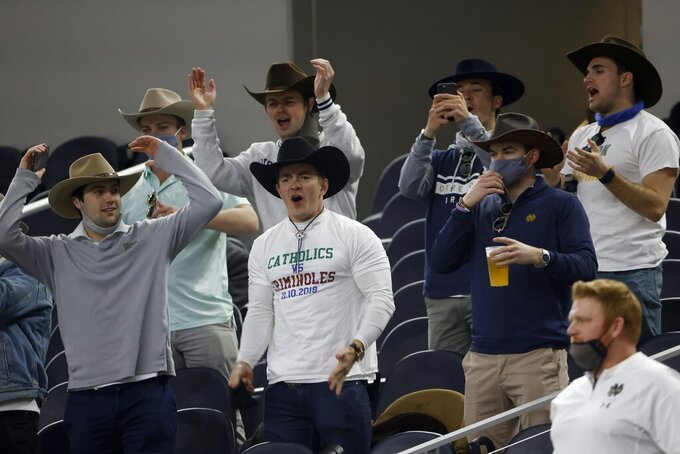 Fans wearing cowboy hats watch warmups before the Rose Bowl NCAA college football game between Notre Dame and Alabama in Arlington, Texas, Friday, Jan. 1, 2021. (AP Photo/Ron Jenkins)