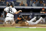 Baltimore Orioles' Ryan McKenna, right, scores a run past New York Yankees catcher Gary Sanchez (24) during the 10th inning of a baseball game on Friday, Sept. 3, 2021, in New York. (AP Photo/Adam Hunger)