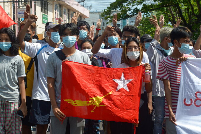 """Anti-coup protesters hold the flag of the National League of Democracy party of ousted Myanmar leader Aung San Suu Kyi, while others flash the three-fingered salute during a """"flash mob"""" rally in Bahan township in Yangon, Myanmar, Sunday, May 9, 2021. Myanmar's junta has labeled a shadow government of lawmakers and politicians ousted in a February coup and a people's defense force that is being set up to confront security forces as terrorist groups. (AP Photo)"""