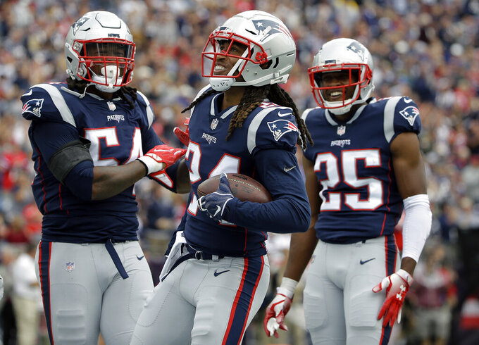 FILE - In this Sept. 9, 2018, file photo, New England Patriots defensive back Stephon Gilmore, center, celebrates his interception with Dont'a Hightower, left, and Eric Rowe, right, during the first half of an NFL football game against the Houston Texans in Foxborough, Mass. 2018 has been a signature season for one of the quietest players in their locker room. Gilmore earned All-Pro honors for the first time in his career and taken the leadership reins of a secondary that lost Malcolm Butler in free agency this past offseason. (AP Photo/Steven Senne, File)