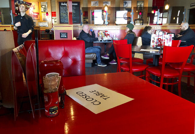 FILE - In this March 15, 2020, file photo, a Red Robin restaurant in Tigard, Ore., has closed some tables in order to maintain social distancing between diners per CDC guidelines. Oregon Gov. Kate Brown on Friday, Nov. 13, 2020, announced a statewide two-week