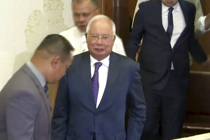 In this image made from video,Malaysian's ex-Prime Minister Najib Razak leaves a courtroom in Kuala Lumpur, Monday, Aug. 19, 2019. The second trial of ex-Prime Minister Najib linked to the multibillion-dollar looting of the 1MDB state investment fund was delayed Monday by a week to allow his first trial to end.(AP Photo)