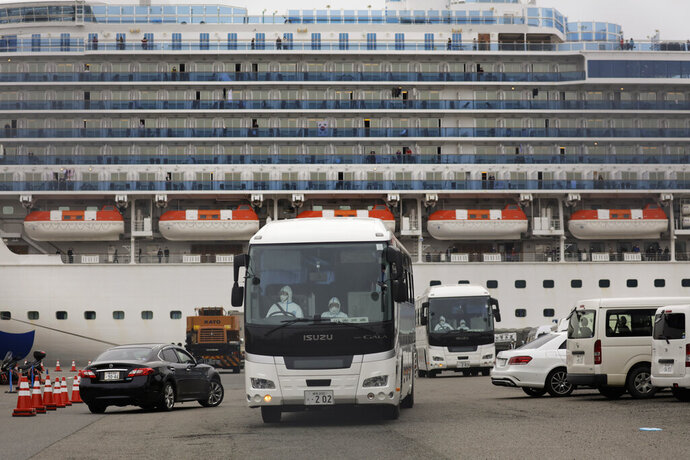 Two buses leave a port where the quarantined Diamond Princess cruise ship is docked Saturday, Feb. 15, 2020, in Yokohama, near Tokyo. A viral outbreak that began in China has infected more than 67,000 people globally. The World Health Organization has named the illness COVID-19, referring to its origin late last year and the coronavirus that causes it. (AP Photo/Jae C. Hong)