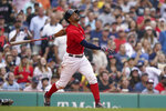 Boston Red Sox's Xander Bogaerts hits a sacrifice fly allowing Enrique Hernandez to score in the eighth inning of a baseball game against the New York Yankees, Sunday, July 25, 2021, in Boston. The Red Sox won 5-4. (AP Photo/Steven Senne)