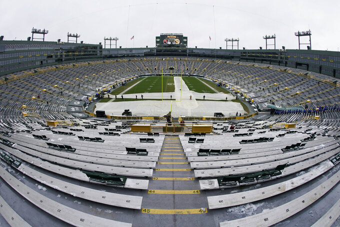 Workers removed the tarp on Lambeau Field before the NFC championship NFL football game between the Tampa Bay Buccaneers and Green Bay Packers in Green Bay, Wis., Sunday, Jan. 24, 2021. (AP Photo/Morry Gash)