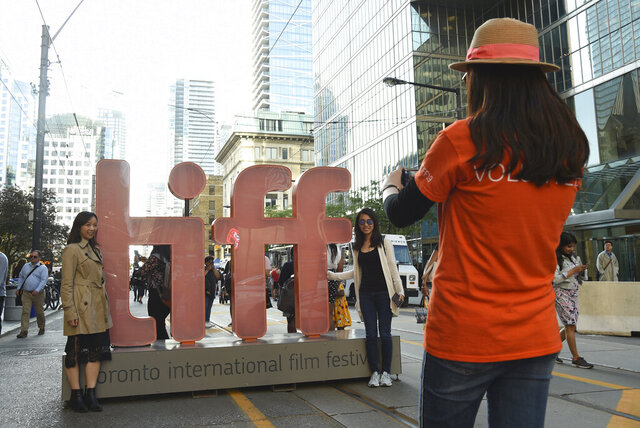 FILE - In this Sept. 5, 2019 file photo, a volunteer takes a photo of people next to signage promoting the Toronto International Film Festival  in Toronto. The festival, one of the leading launching pads for fall movies and Oscar contenders, announced plans for a smaller 2020 edition with virtual red carpet premieres and drive-in screenings. It is typically a sprawling city-wide affair that hosts between 250-400 feature-length films and the debuts of many of the fall movie season's top releases. (Photo by Chris Pizzello/Invision/AP, File)