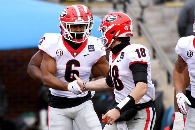 Georgia running back Kenny McIntosh (6) is congratulated by quarterback JT Daniels (18) after scoring during the first half of an NCAA college football game against Missouri Saturday, Dec. 12, 2020, in Columbia, Mo. (AP Photo/L.G. Patterson)